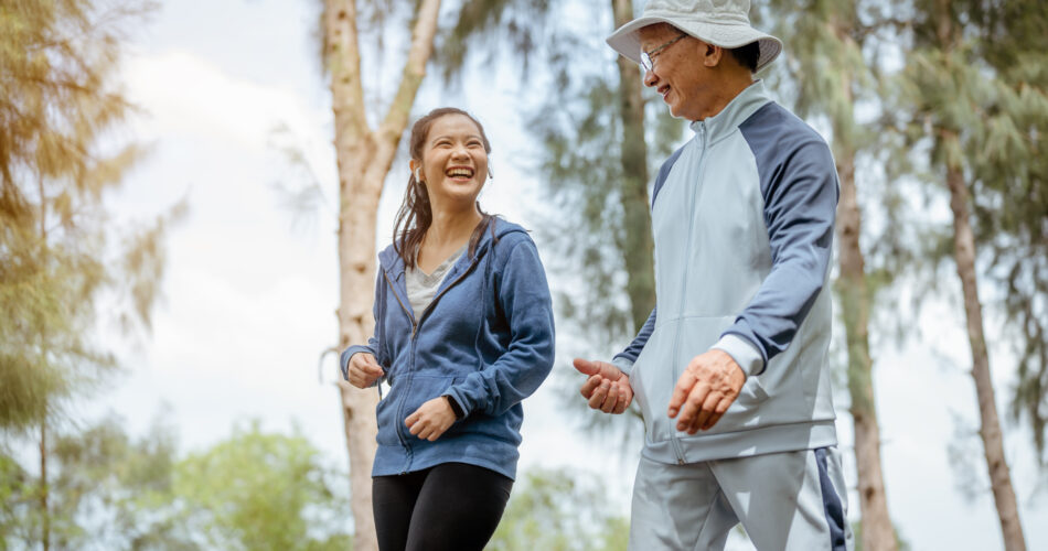 A woman and grandfather are walking jogging on the street at the park. Grandfather talk about the story of  past life experiences. Healthy and lifestyle concept.