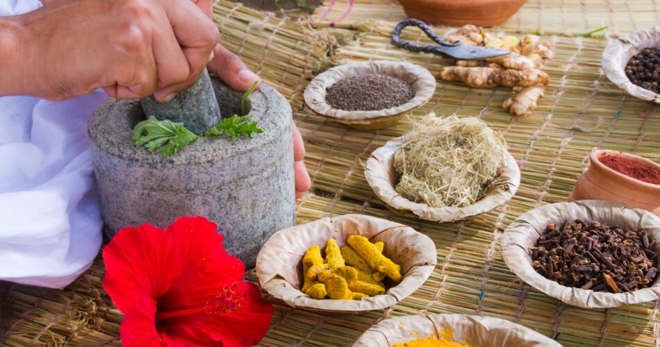 A young man preparing Ayurvedic medicine in the traditional manner in India.