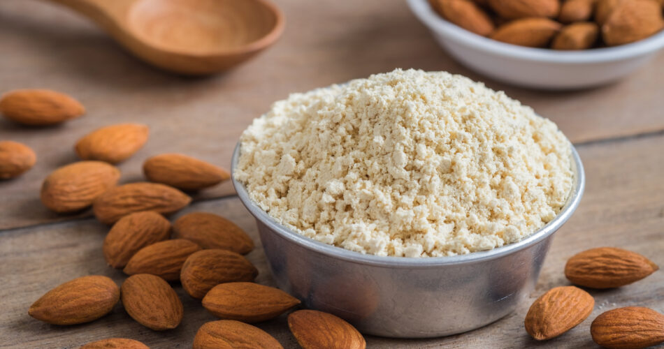 Almond flour in bowl and almonds on wooden table