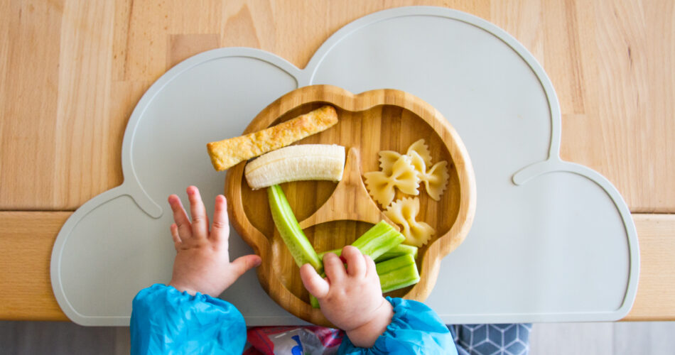 Baby hands grabbing food from plate (bamboo) with finger food (cucumber, pasta, banana) for babies in top view, showing the concept of baby-led weaning, nutrition without pureed food