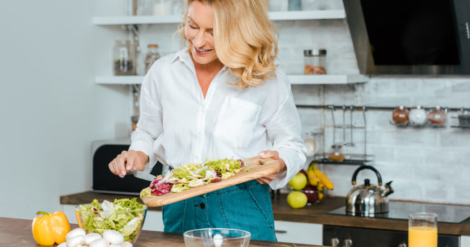beautiful adult woman making healthy salad at kitchen