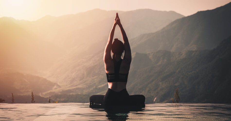 Beautiful Attractive Asian woman practice yoga Lotus pose on the pool above the Mountain peak in the morning in front of beautiful nature views,Feel so comfortable and relax in holiday,Warm tone