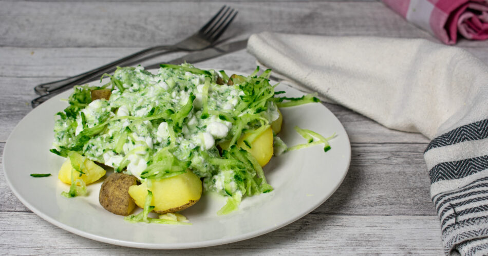 boiled potatoes with skin served with cottage cheese and rasped fresh cucumber on a white plate - ready to eat