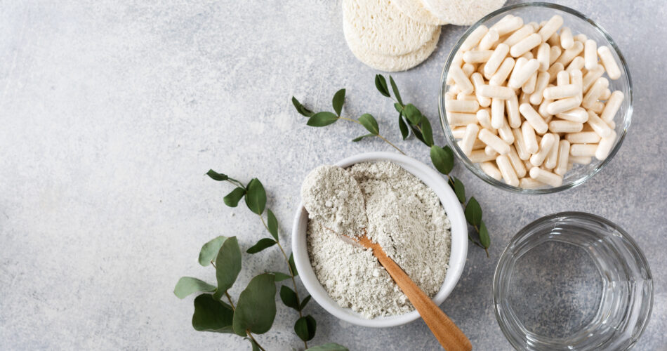 Closeup collagen for preparing a cosmetic mask in ceramic bowl with spoon and capsules for diet food, loofah sponges and dry eucalyptus branches on old gray concrete background. Flat lay with copy space.