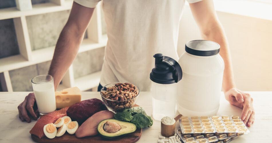 Bijgesneden beeld van knappe jonge sportman die sportvoeding in keuken thuis voorbereidt