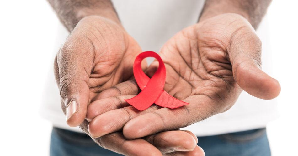 cropped shot of african american man holding aids awareness red ribbon isolated on white