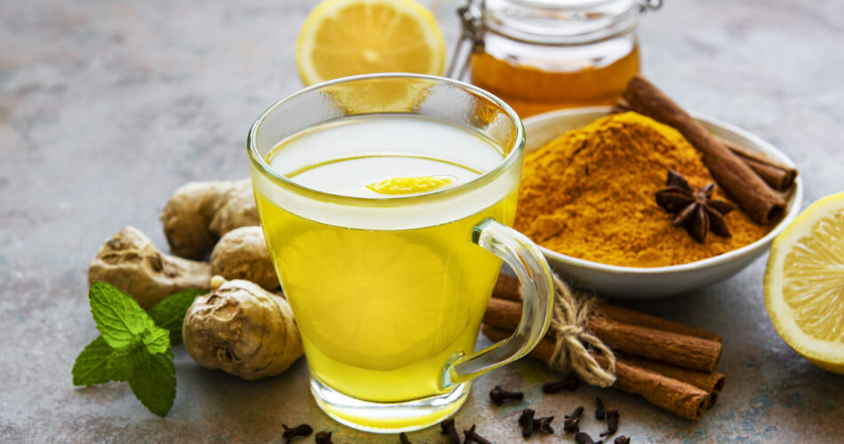 Energy tonic drink with turmeric, ginger, lemon and honey on a grey concrete background