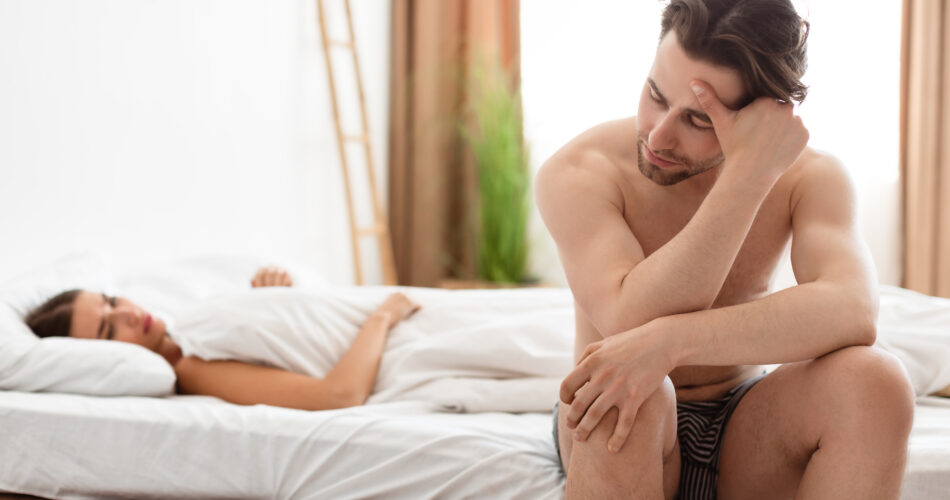 Erectile Dysfunction. Unhappy Man Having Erection Problems While His Girlfriend Lying In Bed In Bedroom At Home. Sexual Failure And Stress. Impotence, Male Health Issue. Selective Focus
