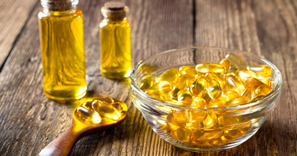 Fish oil capsules on wooden background, vitamin D supplement
