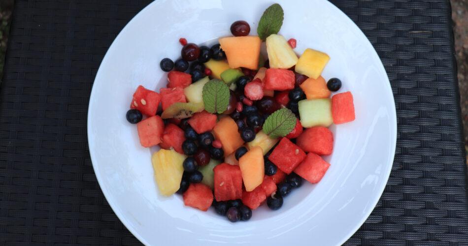 Salada de frutas frescas e suculentas em cores vivas, decorada com folhas de menta fresca
