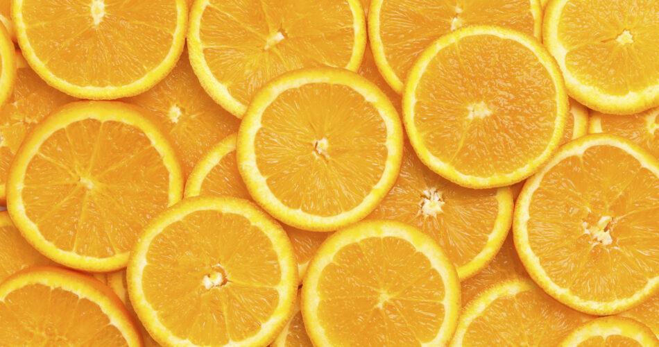 Fresh orange fruit slices pattern background, close up