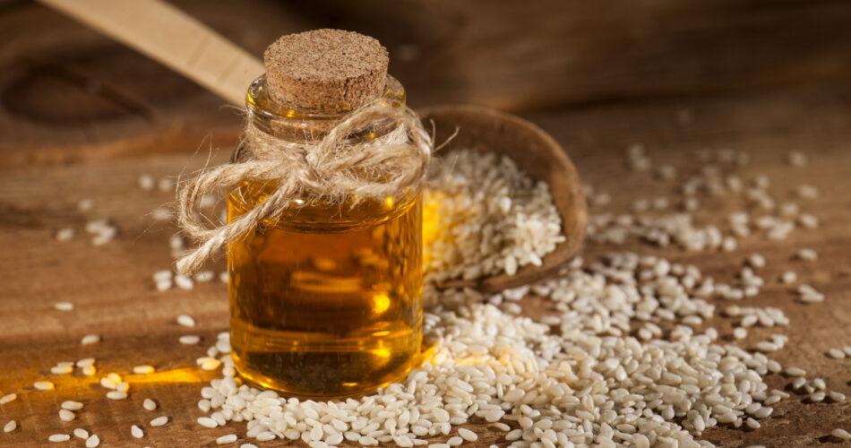 Verse sesamolie in een glazen fles en zaden in een houten lepel op houten achtergrond