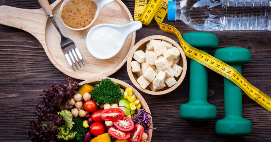 Ensalada de verduras frescas y alimentos saludables para el equipo de deporte para las mujeres de la dieta de adelgazamiento con el grifo de medida para la pérdida de peso en el fondo de madera. Concepto de deporte saludable