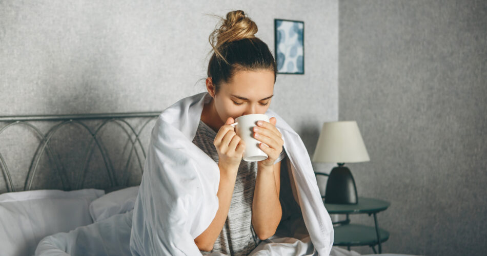 Girl drinks a drink from a mug in bed wrapped in a blanket. She is enjoying or she is not awake or sick.