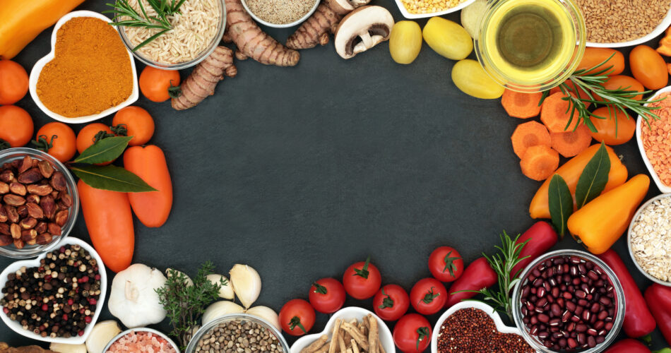 Health food  background border with fruit, vegetables, grains, pulses, herbs, spices, seeds, nuts, himalayan salt and olive oil. Foods high in antioxidants, anthocyanins,smart carbohydrates, vitamins and minerals.