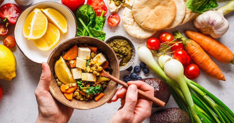 Healthy vegetarian food background. Vegetables, hummus, pesto and lentil curry with tofu.