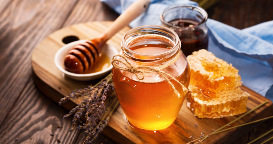 Jar of liquid honey with honeycomb inside and bunch of dry lavender over old wooden table. Dark rustic style, selective focus