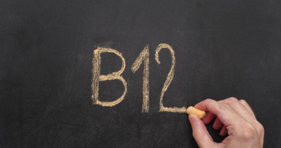 Man writing word B12 on chalkboard. Vitamin B12 Concept. Close up.
