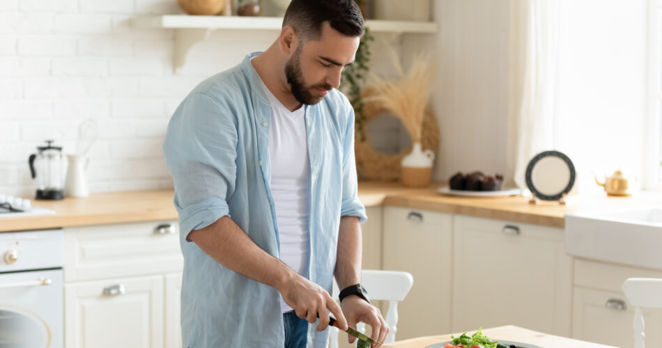 Millennial man stand at modern kitchen table chop vegetables prepare fresh vegetable salad for dinner or lunch, young male cooking at home make breakfast follow healthy diet, vegetarian concept