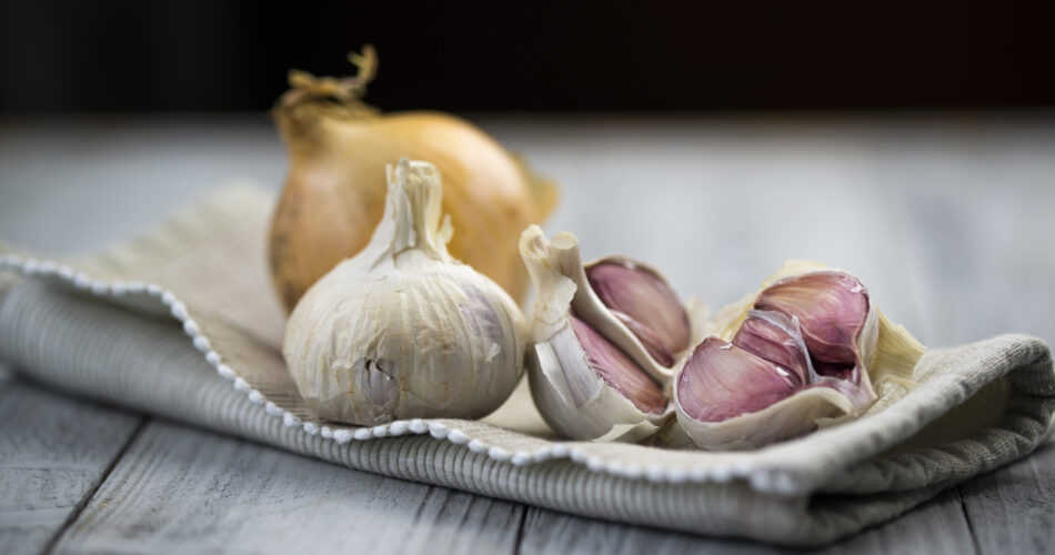 Organic garlic and onion on wooden background with copy space