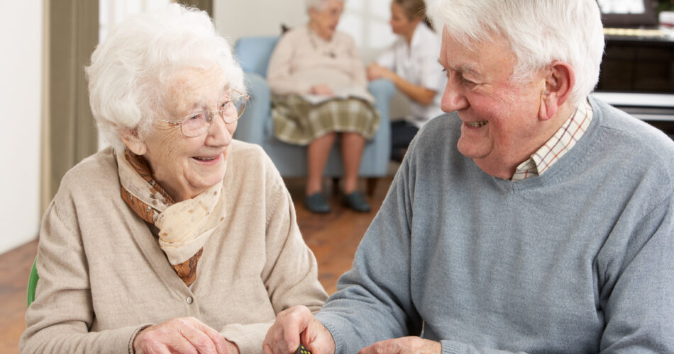 Senior Couple Playing Dominoes At Day Care Centre