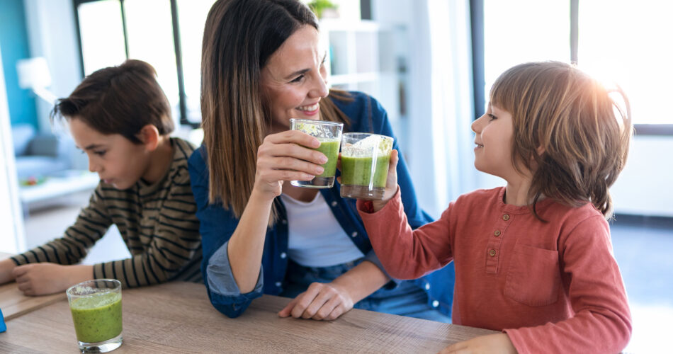 Shot of pretty young mother with her son toasting with detox smoothie in the kitchen at home.