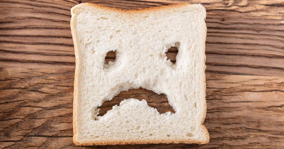 Plakje brood met een ongelukkig gezicht uitgesneden op houten bureau