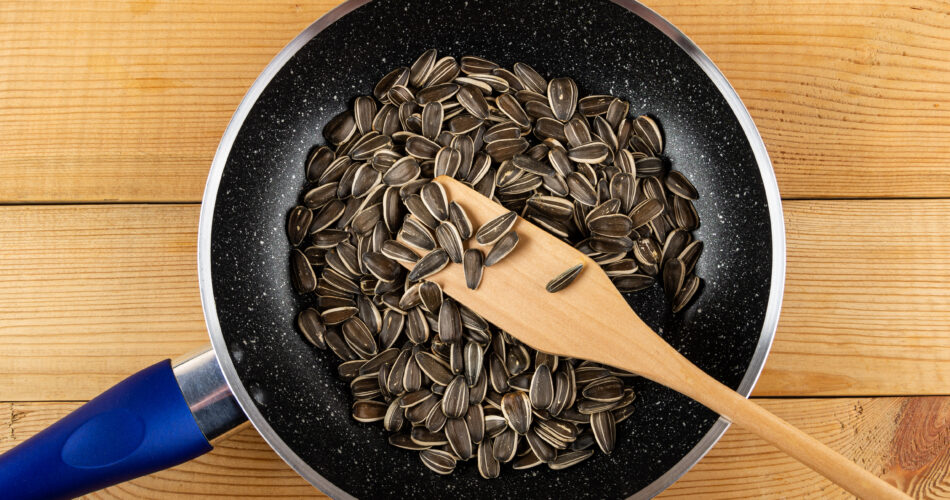 Spatula in frying pan with sunflower seeds on wooden table. Top view