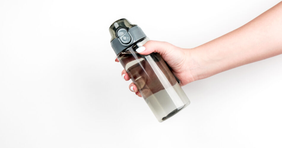 Sports water bottle in a woman's hand on a light background. Concept of water consumption, healthy lifestyle. Copyspace