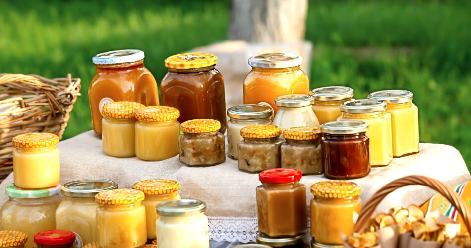 There are a lot of glass jars with honey on the table with a linen tablecloth on the street against the background of juicy greenery on a sunny summer day