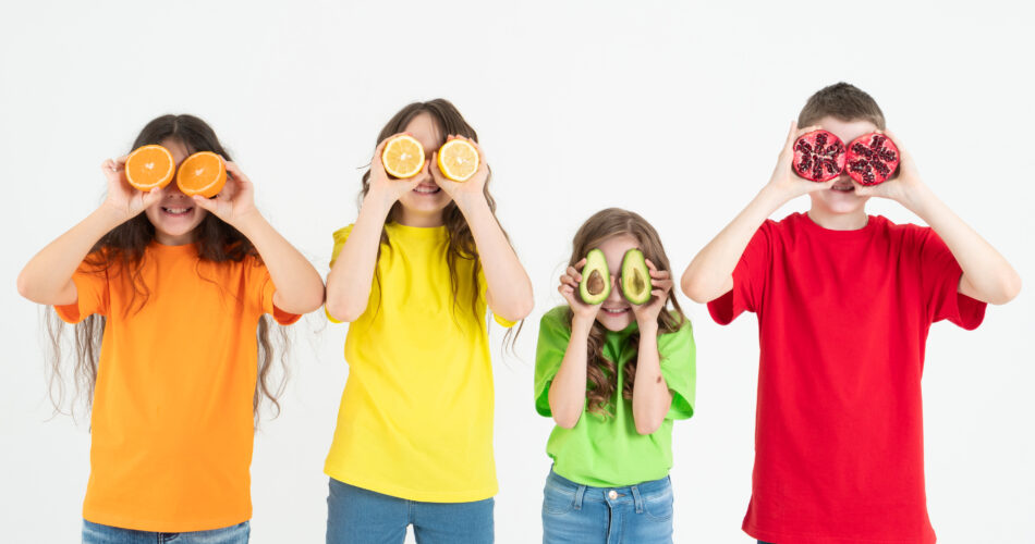 Three girls and a boy using fruits as glasses on a on a white background. Group of happy children with orange, lemon, avocado and pomegranate in hands