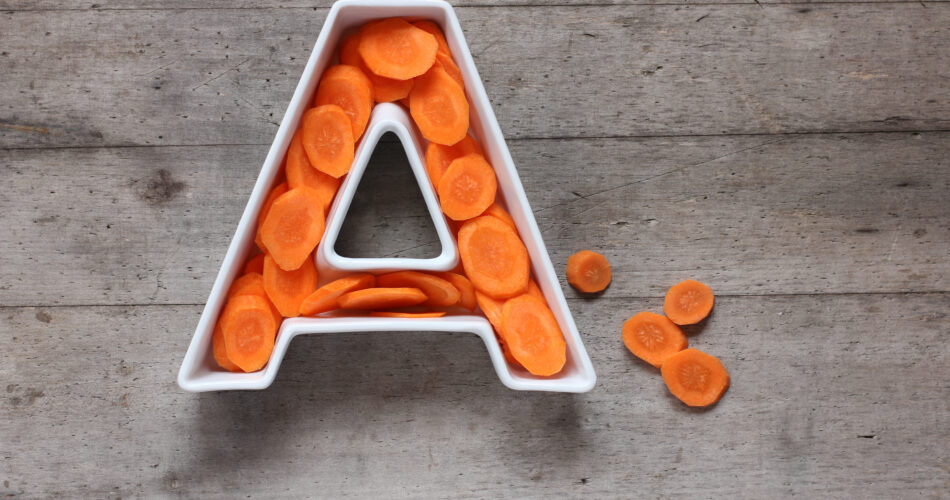 Vitamin A in food concept. Plate in the shape of the letter A with sliced fresh carrots on wooden background. Flat lay or top view.
