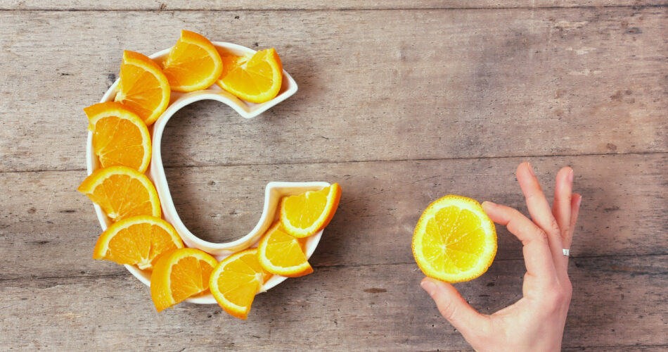 Vitamin C or Ascorbic acid nutrient in food concept. Plate in shape of letter C with orange slices and woman's hand with citrus making sign OK on wooden background. Flat lay or top view.