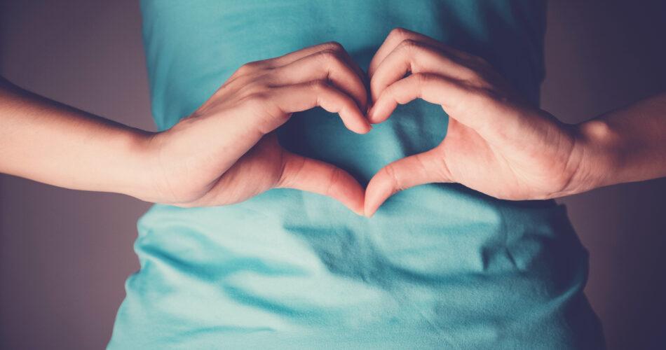 Frauenhände, die eine Herzform auf ihrem Bauch bilden, gesunde Darmentleerung, Probiotika für die Darmgesundheit