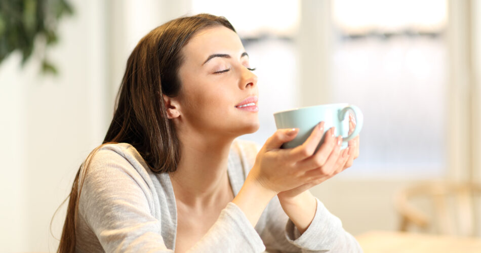 Woman smelling coffee aroma at home