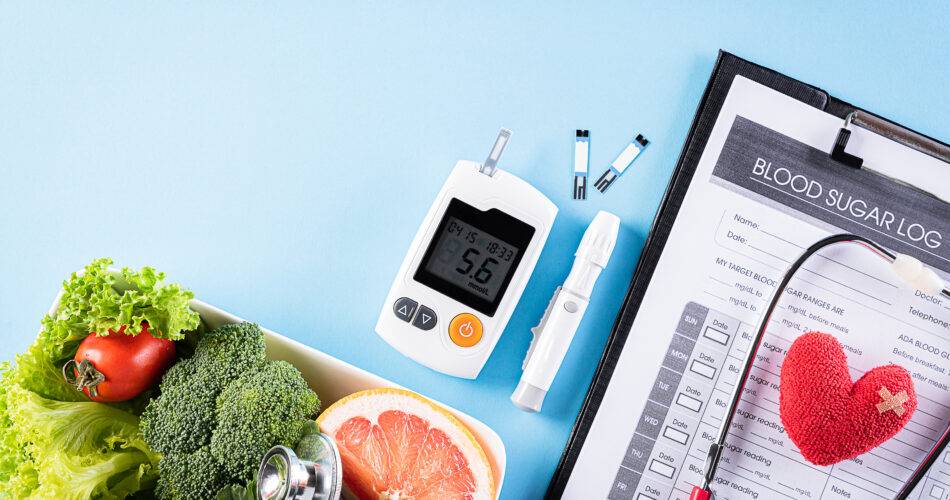 World diabetes day and healthcare concept. Patient's blood sugar control, diabetic measurement, and healthy food eating nutrition with red heart on blue background.