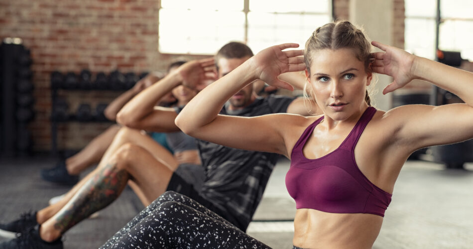 Young fitness woman doing abdominal exercise at gym. Concentrated people in a row doing sit ups on yoga mat. Training class doing situps at cross training center.