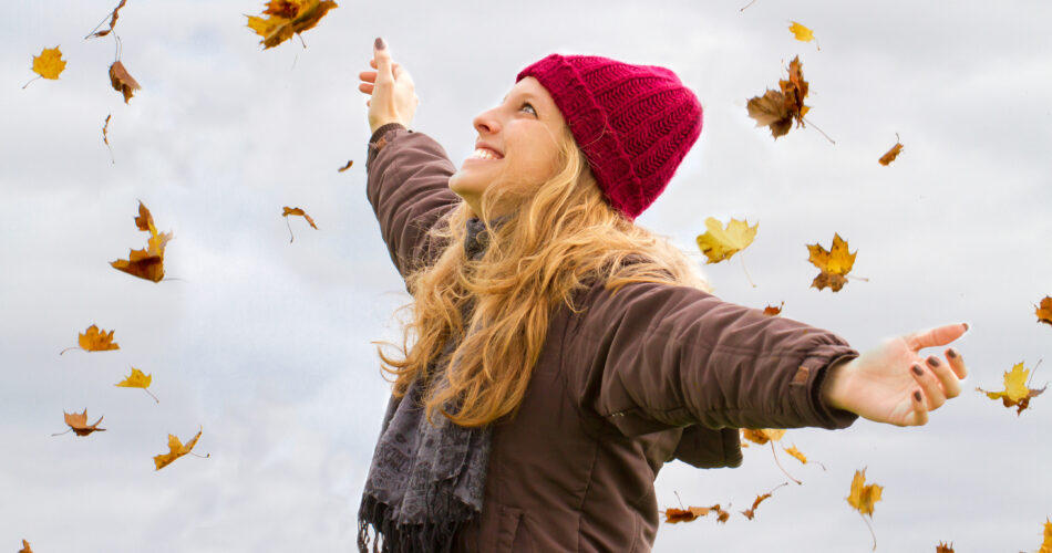 Young, happy woman with raised arms in autumn