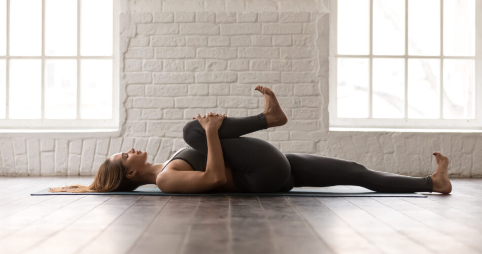Calm woman with closed eyes practicing yoga, attractive girl in grey sportswear, pants and bra lying in Knees to Chest pose, doing Apanasana exercise, working out at home or in yoga studio