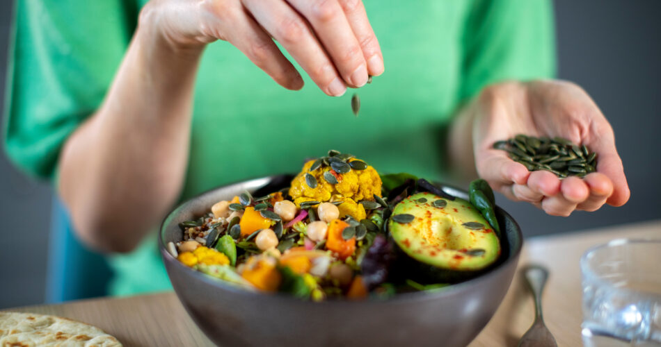 Close Up Of Woman Adding Pumpkin Seeds To Healthy Vegan Meal In Bowl