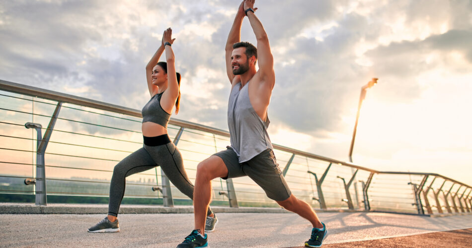 Couple doing sport together on the street. Yoga in the morning