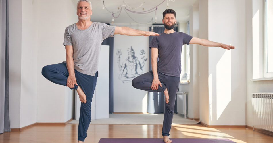 Front view of two yogis doing a tree pose with their arms at the sides