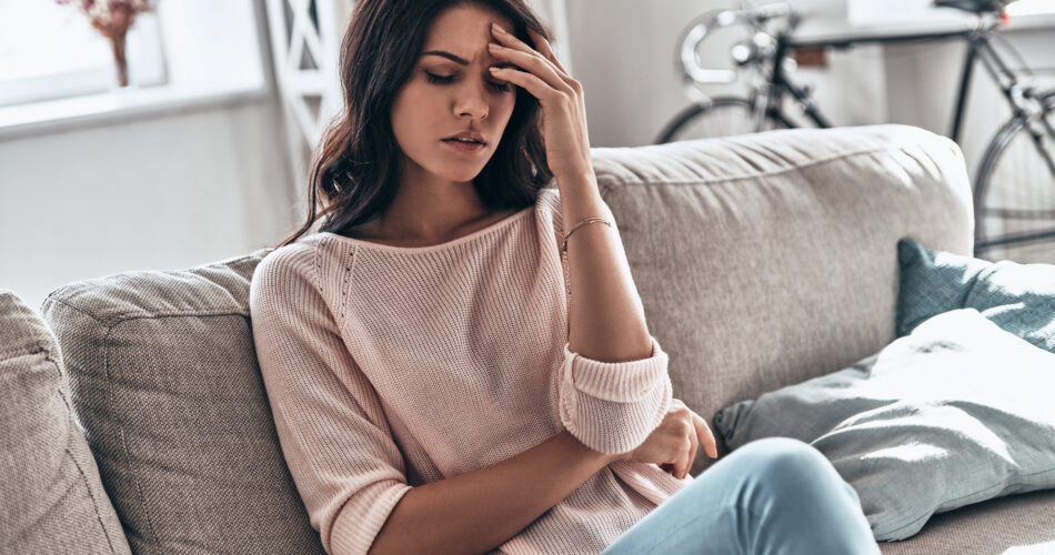 Frustrated young woman suffering from the headache while sitting on the sofa at home