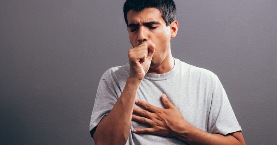 Man coughing into his fist, isolated on a gray background
