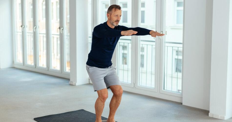 Man doing balance and muscle control exercises in a bright spacious urban gym in a health and fitness concept