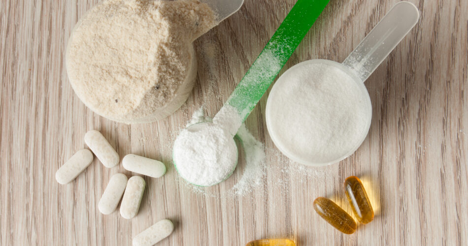 scoop of protein, bcaa and creatine, omega3 in pills on wooden background