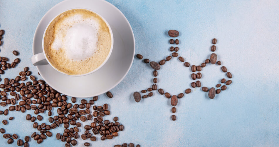 a cup of coffee with caffeine molecule created by coffee beans. Chemical formula of Caffeine with roasted coffee spill out of cup on blue wooden background.