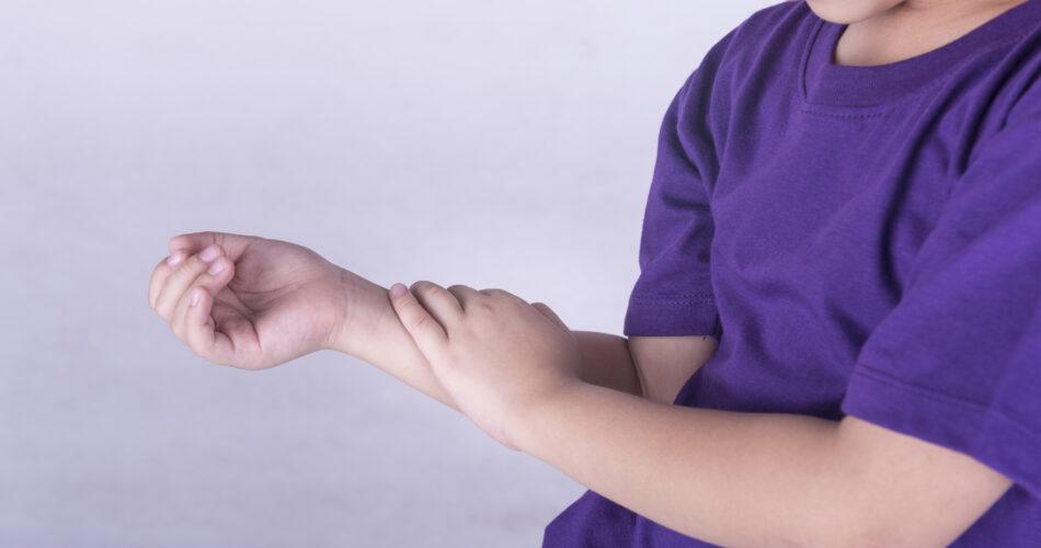 Jongens controleren zijn arm met spierpijn.