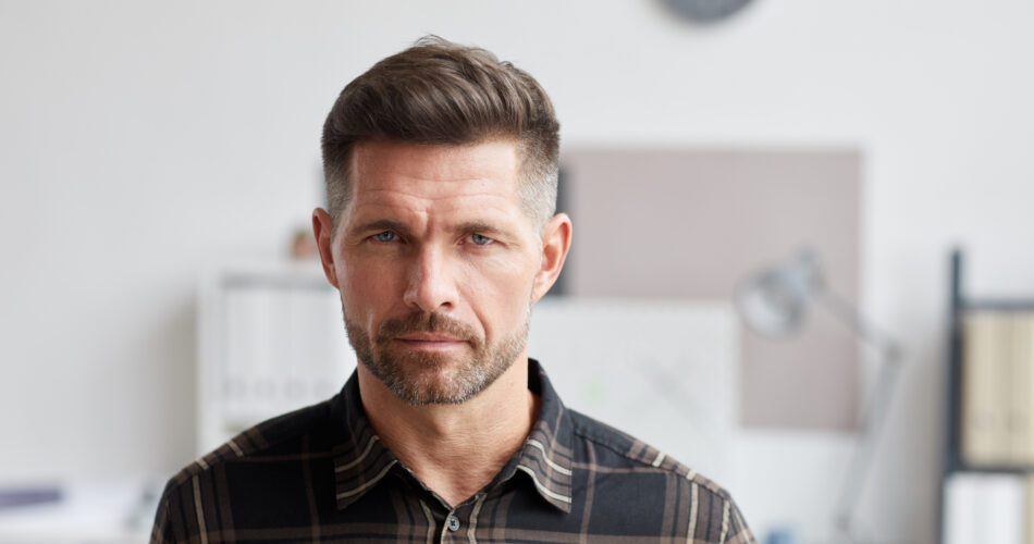 Close up portrait of mature bearded man looking at camera while standing in architects office, copy space