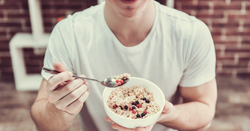Handsome young guy is smiling while eating porridge with berries in kitchen at home